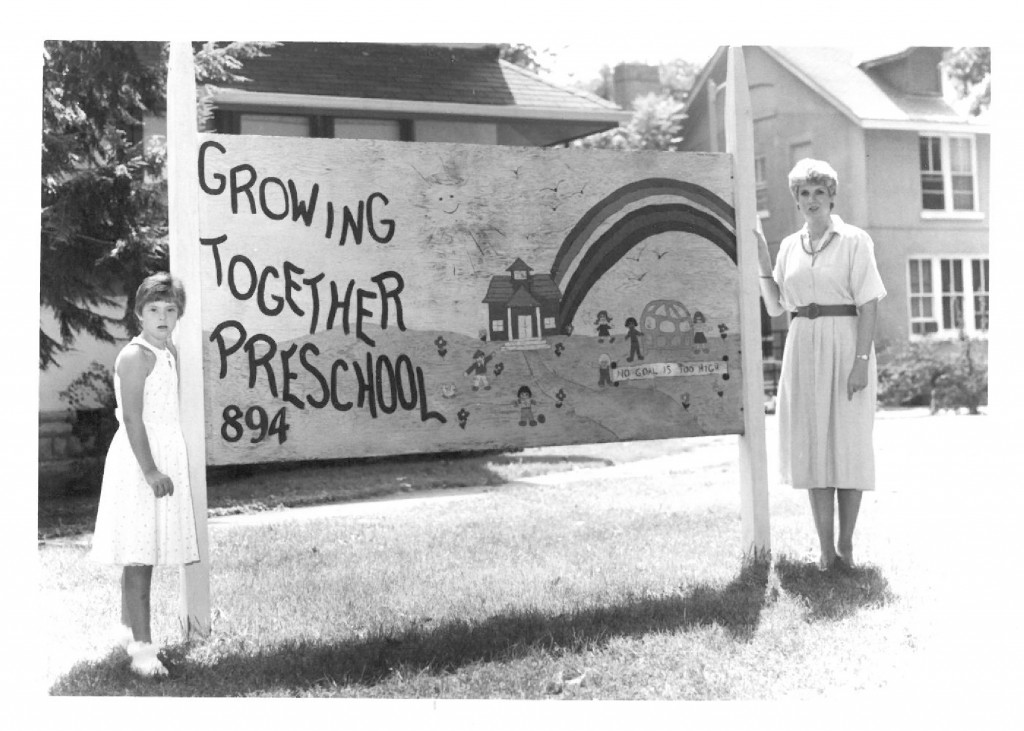 Leeann and her mother, Betsy, pose for a picture by the original Growing Together Preschool sign.
