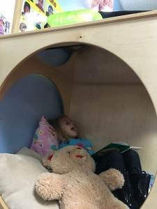 Lily uses the relaxing retreat in her preschool classroom for some quiet alone time after drop-off. She loves snuggling the teddy bear, reading a book and making funny faces in the mirror on top.
