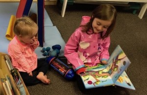 Evie reads to Juno in her classroom at Growing Together Preschool.
